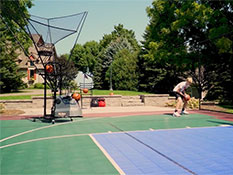 A kid practicing basketball at his own backyard with the help of a Dr Dish shooting machine