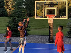 Kids playing a basketball game at their own backyard